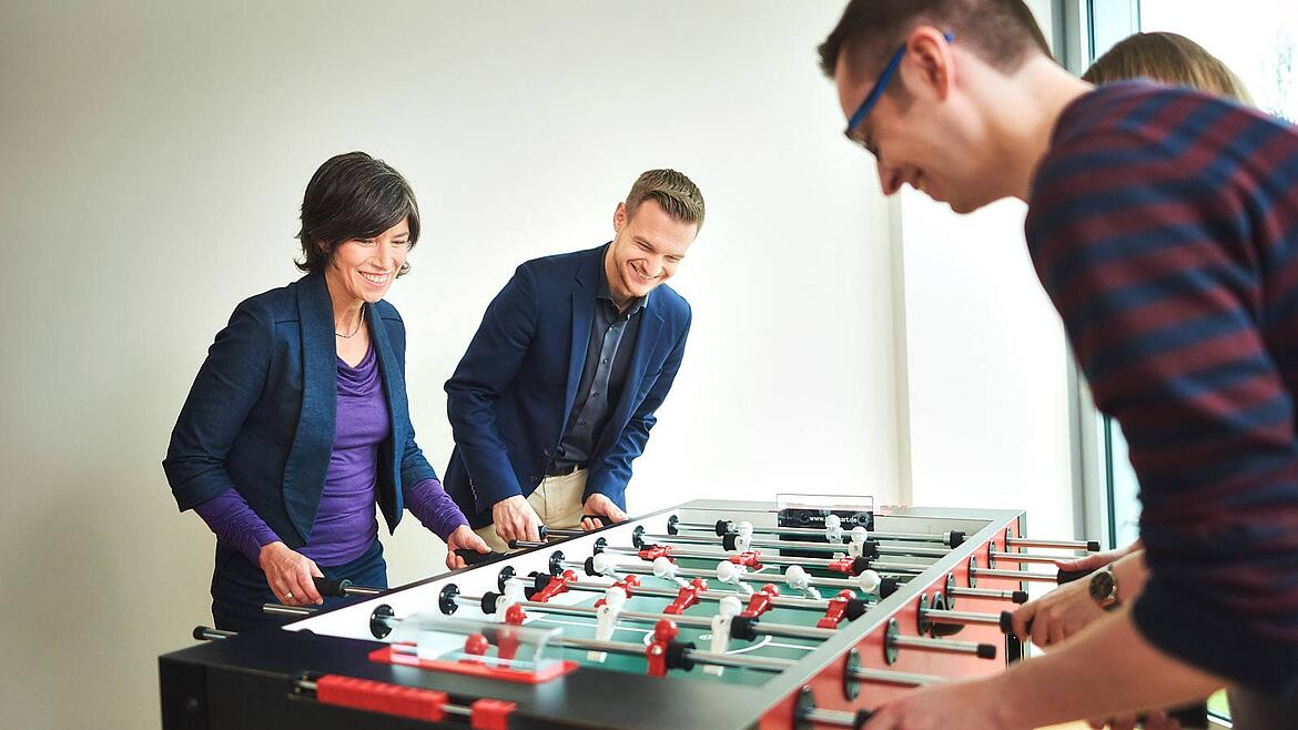 adesso colleagues playing table soccer
